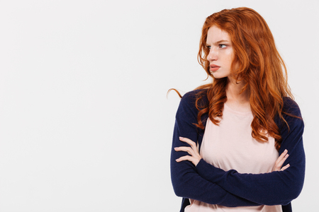 Photo for Photo of angry pretty young redhead lady standing isolated over white wall background with arms crossed. Looking aside. - Royalty Free Image