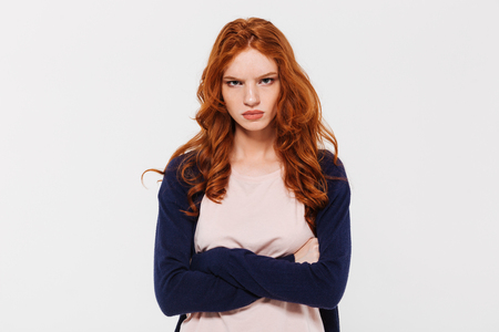 Photo for Image of angry pretty young redhead lady standing isolated over white wall background with arms crossed. Looking camera. - Royalty Free Image