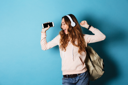 Photo for Portrait of a joyful attractive girl student with backpack listening to music with headphones while showing blank screen mobile phone and dancing isolated over blue background - Royalty Free Image