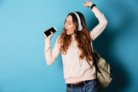 Photo pour Portrait of a cheerful happy girl student with backpack listening to music with headphones while showing blank screen mobile phone and dancing isolated over blue background - image libre de droit