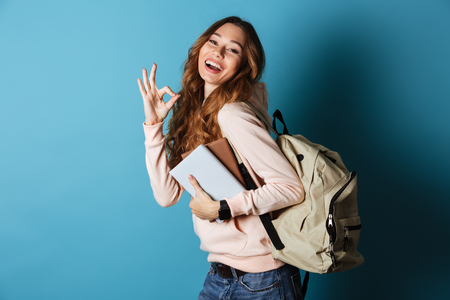 Foto de Portrait of a happy friendly girl student with backpack holding books and showing ok gesture isolated over blue background - Imagen libre de derechos