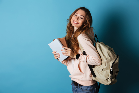 Photo pour Portrait of a smiling cheery girl student with backpack holding books and looking at camera isolated over blue background - image libre de droit