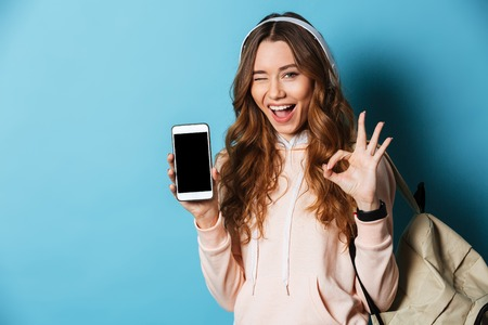 Photo for Portrait of a happy cheerful girl student with backpack listening to music with headphones while holding blank screen mobile phone and showing ok gesture isolated over blue background - Royalty Free Image