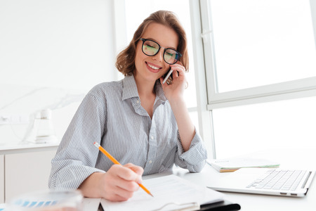 Photo pour Beautiful smiling girl in glasses talking on mobile phone while working with documents at home - image libre de droit