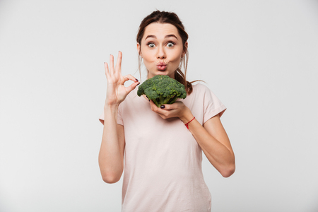 Photo for Portrait of a cheerful pretty girl holding broccoli and showing ok gesture isolated over white background - Royalty Free Image