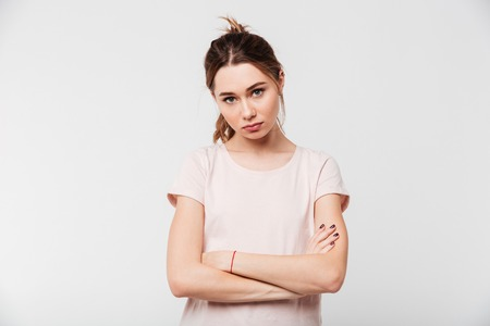 Photo for Portrait of an upset pretty girl standing with arms folded isolated over white background - Royalty Free Image