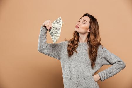 Foto de Portrait of gorgeous brunnete woman with closed eyes waving with fan of money, isolated over beige background - Imagen libre de derechos