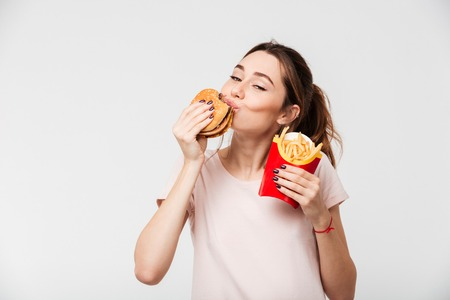 Foto de Close up portrait of a satisfied pretty girl eating french fries and a burger isolated over white background - Imagen libre de derechos