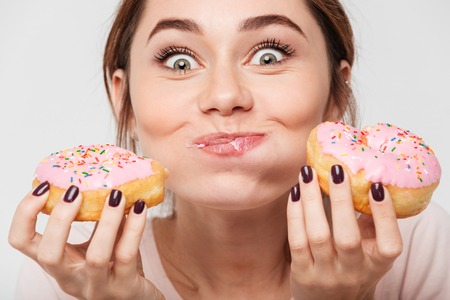 Photo for Close up portrait of a satisfied pretty girl eating donuts isolated over white background - Royalty Free Image