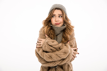 Photo for Displeased freezing young woman dressed in warm sweater and scarf standing isolated over white wall background. Looking aside. - Royalty Free Image