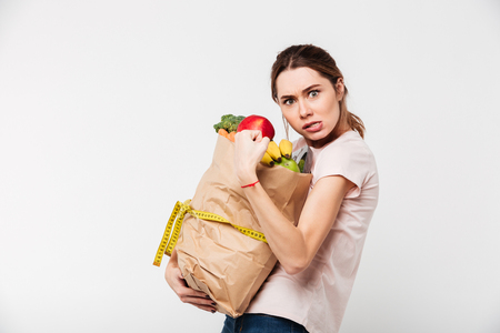 Foto de Portrait of a greedy girl holding bag with groceries isolated over white background - Imagen libre de derechos
