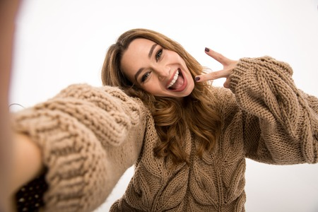 Photo pour Picture of happy cute woman dressed in warm sweater sitting on floor isolated over white wall background make selfie by camera showing peace gesture. - image libre de droit