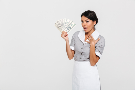 Photo pour Portrait of amazed young housekeeper in uniform holding fan of dollar banknotes, looking at camera, isolated over white background - image libre de droit