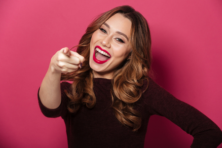 Foto de Image of cheerful young beautiful woman standing isolated over pink background. Looking camera pointing. - Imagen libre de derechos