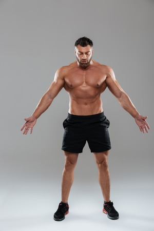 Foto de Full length portrait of a confident strong shirtless male bodybuilder posing while standing with outstretched hands isolated over gray background - Imagen libre de derechos