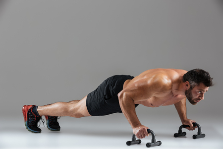 Photo pour Full length portrait of a muscular strong shirtless male bodybuilder doing push-ups with bars isolated over gray background - image libre de droit