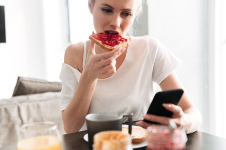 Foto de Focused blonde lady eating bread with jam and using smartphone while have breakfast in kitchen - Imagen libre de derechos
