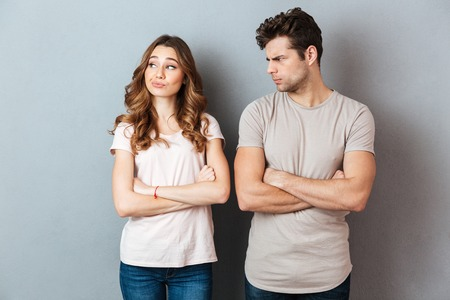 Photo for Disappointed young couple standing with arms folded over gray wall - Royalty Free Image