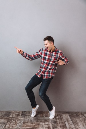 Photo for Full length image of Happy man in shirt and jeans dancing over gray background - Royalty Free Image