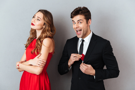 Photo pour Portrait of a happy excited man taking out box with engagement ring from a jacket while his girlfriend standing near over gray wall background - image libre de droit