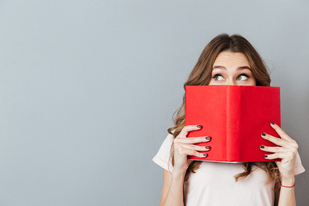 Photo pour Portrait of a pretty young girl hiding behind an open book and looking away isolated over gray wall background - image libre de droit