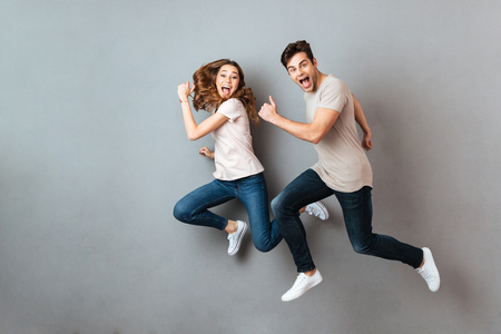 Foto de Full length portrait of a cheerful young couple jumping and running over gray wall - Imagen libre de derechos