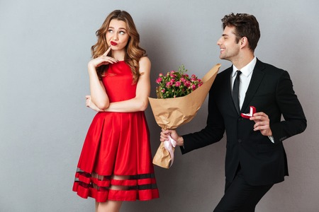 Photo pour Portrait of a joyful man proposing to a unsatisfied girl with flowers and an engagement ring over gray wall background - image libre de droit