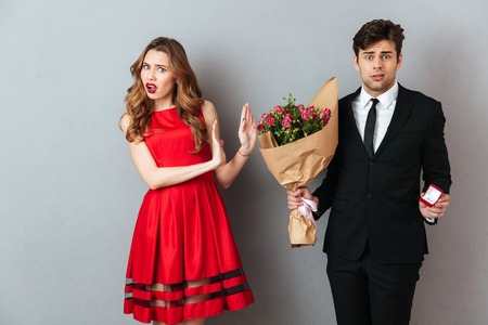 Photo for Portrait of a frustrated man proposing to a girl with flowers and an engagement ring and getting denied over gray wall background - Royalty Free Image