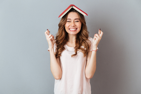 Foto de Portrait of a happy girl holding book on her head with crossed fingers for good luck isolated over gray wall background - Imagen libre de derechos