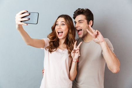 Foto de Portrait of a cheerful young couple showing peace gesture while standing and taking a selfie over gray wall - Imagen libre de derechos