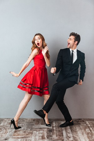 Photo pour Full length portrait of a happy excited couple dressed in formal wear dancing together and having fun over gray wall background - image libre de droit