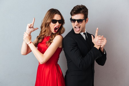 Photo pour Portrait of an furious young couple dressed in formal wear and sunglasses standing back to back and showing gun gesture over gray wall background - image libre de droit