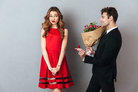 Photo for Portrait of a smiling man proposing to a girl with flowers and an engagement ring over gray wall background - Royalty Free Image