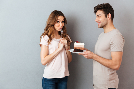 Photo for Portrait of a smiling man giving his girlfriend a piece of cake on a plate isolated over gray wall background - Royalty Free Image