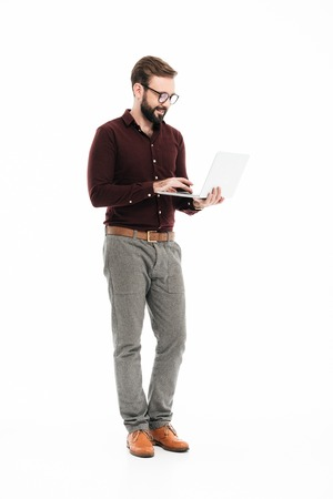 Photo pour Full length portrait of a confident successful man in eyeglasses using laptop computer while standing isolated over white background - image libre de droit