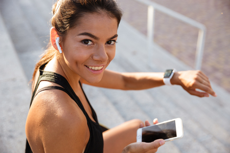 Photo pour Portrait of a smiling fitness girl in earphones sitting on stairs outdoors with mobile phone and checking her smart watch - image libre de droit