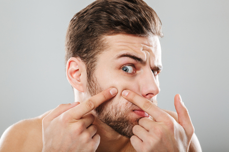 Photo for Close up portrait of a man squeezing pimples on his cheek isolated over gray background - Royalty Free Image