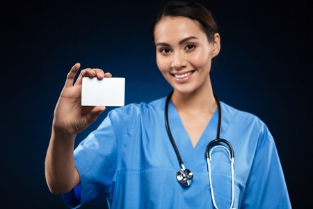 Foto de Pretty brunette doctor with stethoscope showing blank badge and smiling isolated over black - Imagen libre de derechos