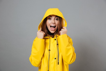 Photo pour Portrait of a joyful girl dressed in raincoat posing with hood on her head and looking at camera isolated over gray background - image libre de droit