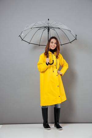 Photo pour Full length portrait of a cheery girl dressed in raincoat and rubber boots posing while standing with an open umbrella isolated over gray background - image libre de droit