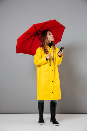 Photo pour Full length portrait of a smiling girl dressed in raincoat and rubber boots posing while standing with an open umbrella and holding mobile phone isolated over gray background - image libre de droit