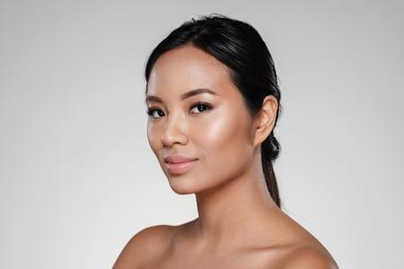 Foto de Beauty portrait of an attractive half asian woman looking at camera isolated over gray background - Imagen libre de derechos