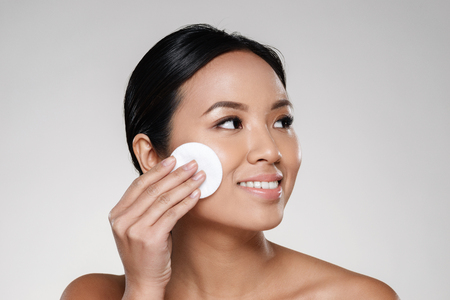 Foto de Beauty portrait of a happy half asian woman removing make-up with a cotton pad and looking away at copy space isolated over gray background - Imagen libre de derechos
