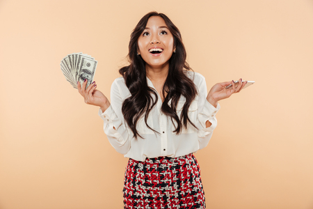 Foto de Portrait of a happy asian woman holding bunch of money banknotes isolated over beige background - Imagen libre de derechos
