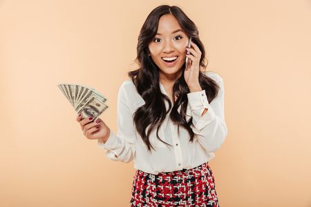 Foto de Portrait of an excited asian woman holding bunch of money banknotes and talking on mobile phone isolated over beige background - Imagen libre de derechos