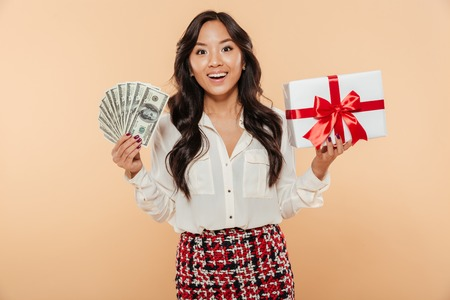 Foto de Portrait of a happy asian woman holding bunch of money banknotes and a gift box isolated over beige background - Imagen libre de derechos