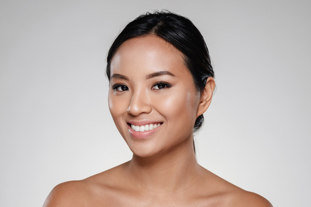 Foto de Beauty portrait of a smiling half asian woman looking at camera isolated over gray background - Imagen libre de derechos