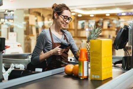 Photo pour Smiling female cashier scanning grocery items at supermarket - image libre de droit
