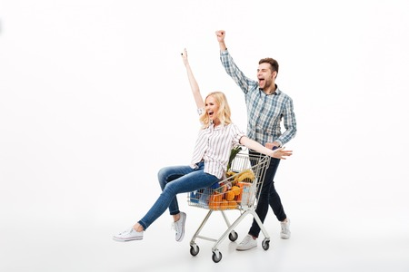 Photo for Full length portrait of a joyful couple having fun with a supermarket trolley isolated over white background - Royalty Free Image