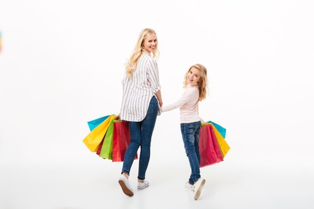 Photo for Back view of a smiling mother and her little daughter walking with shopping bags and looking at camera over shoulder isolated over white background - Royalty Free Image